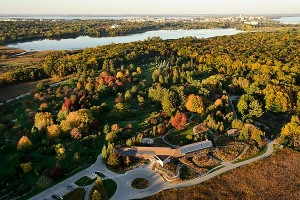 The UW Arboretum's Visitor Center (formerly called the McKay Center) is pictured in an aerial view of the University of Wisconsin-Madison campus during an autumn sunset on Oct. 5, 2011. From foreground to horizon are Curtis Prairie, Longnecker Gardens, Lake Wingra, and the UW-Madison campus and downtown Madison skyline. The photograph was made from a helicopter looking northeast. (Photo by Jeff Miller/UW-Madison)
